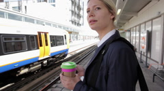 Businesswoman on platform waiting for train Stock Footage