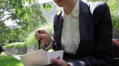 Businesswoman eating lunch in city park Stock Footage