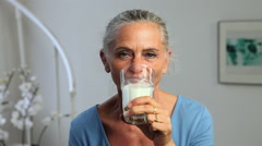 Mature woman drinking a glass of milk - stock footage
