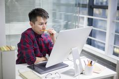 Chinese illustrator working in office - stock photo