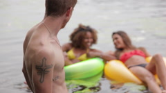Man watching young women floating on rubber rings in lake Stock Footage