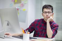 Displeased Chinese illustrator working in office - stock photo