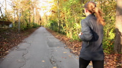 Young woman jogging along path in countryside Stock Footage