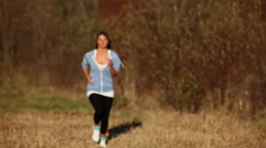 Young woman jogging through countryside Stock Footage