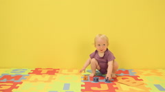 Baby girl playing with toy alphabet letters Stock Footage