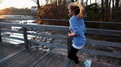 Young woman jogging on bridge, side view Stock Footage