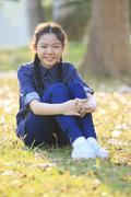 Thai 12s years girl sitting on garden field toothy smiling face happiness emo Stock Photos