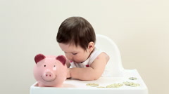 Baby boy sitting in highchair with piggy bank Stock Footage