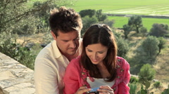 Young couple sitting on wall with camera Stock Footage