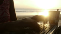 Hands typing on laptop at beach Stock Footage