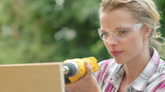 Woman wearing safety goggles drilling plywood with electric drill Stock Footage