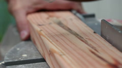 Man sawing through wooden plank with circular saw - stock footage