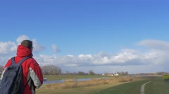 Tourist is Walking Away Along a River by Meadow Backpacker in Red Jacket on a Stock Footage
