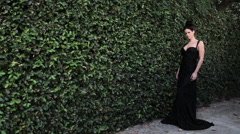 Woman by hedge wearing black evening gown Stock Footage
