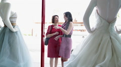 Mother and daughter looking at wedding dress in shop window Arkistovideo