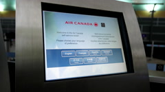 Woman printing out boarding card at Air Canada machine inside YVR Airport - stock footage