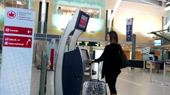 Woman printing out luggage tag at Air Canada machine inside YVR Airport - stock footage