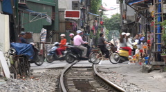Motorbikes and other traffic at a railway crossing and slum area in Hanoi Stock Footage