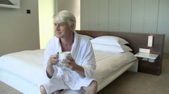Mature man in bedroom with a cup of coffee - stock footage