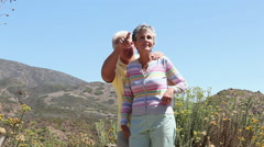 Mature couple in rural setting, looking up and pointing Stock Footage