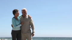Mature couple at the coast in front of blue sky Stock Footage
