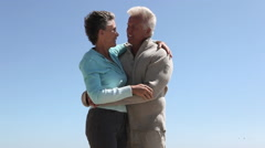 Mature couple against blue sky, hugging and walking away Stock Footage