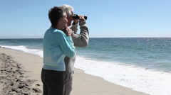 Mature couple at the beach with binoculars Stock Footage