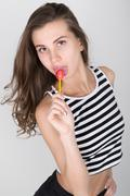 beautiful slim girl in black shorts and a striped top, eating candy. closeup lip - stock photo