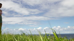 Young couple walking in grass near coast Stock Footage