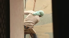 A laborer white washing and repair a high building wall hanging in a rope. Stock Footage