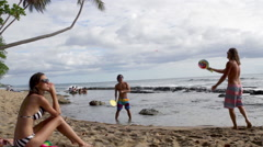 People on beach, men playing bat and ball game Stock Footage