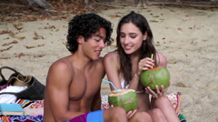 Young couple sitting on beach drinking coconut milk Stock Footage