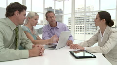 Four businesspeople using laptop in office meeting Stock Footage