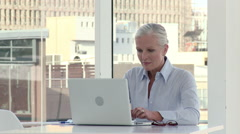 Mature businesswoman using laptop in office Stock Footage