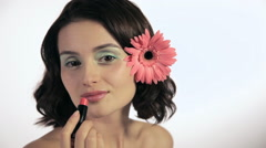 Young woman with flower in hair applying lipstick Stock Footage