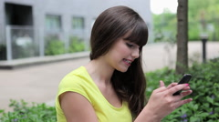 Young woman using cellphone, friend comes and covers her eyes Stock Footage