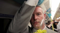 Businessman holding flowers on underground train Stock Footage