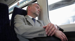 Businessman sleeping on commuter train Stock Footage