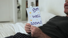 Man reading get well soon card Stock Footage