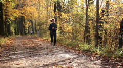 Young woman jogging through forest - stock footage