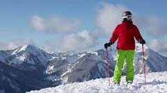 Skier taking in scenery and pointing to mountains with ski pole Stock Footage