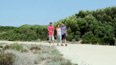 Three friends walking on rural road Stock Footage