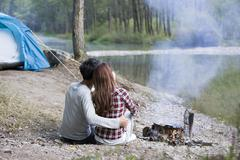 Young Chinese couple sitting beside campfire preparing food Stock Photos