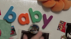 Fridge magnets spelling baby and person swapping magnets Stock Footage