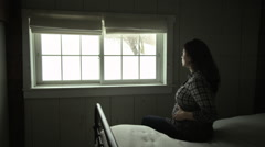 Pregnant woman sitting on bed, looking through window and smiling at camera Stock Footage