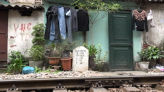 Train tracks, kilometer marker, homes, slum housing, Hanoi, Vietnam Stock Footage