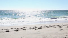Mature couple walking on beach wrapped in blanket Stock Footage