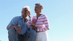 Mature couple blowing bubbles Stock Footage