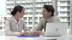 Two businesspeople in office meeting with laptop - stock footage