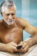 Man in swimming pool with cellphone Stock Photos